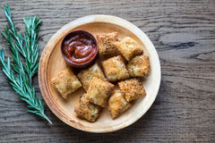Plate with fried ravioli on the wooden board. Plate with fried ravioli and tomato sauce on the wooden board Stock Images