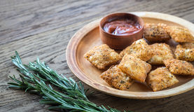 Plate with fried ravioli on the wooden board. Plate with fried ravioli and tomato sauce on the wooden board Royalty Free Stock Photo