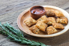 Plate with fried ravioli on the wooden board. Plate with fried ravioli and tomato sauce on the wooden board Royalty Free Stock Images