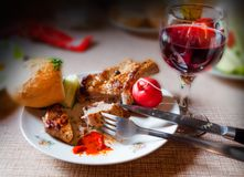 A plate with fried steak, radish, cucumber and bread near a glass with ruby wine. On a blurred background royalty free stock image