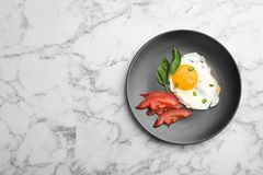 Plate with fried sunny side up egg and tomato on marble background, top view. Space for text stock photography