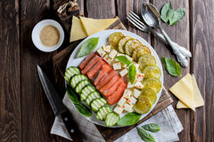 Plate with the fried vegetable marrows salmon salad, cutting. Plate with the fried vegetable marrows salmon salad on rustic table, cutting Royalty Free Stock Image