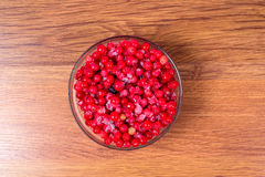 Plate frozen red currants on a wooden background. Harvesting of berries for the winter. Stock Image
