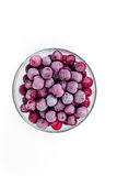 Plate frozen red sweet ripe cherries on a white background. Harvesting of berries for the winter. Stock Image