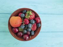Plate, fruit berries, cherry, strawberry, blueberry summer dessert on a blue wooden background. Plate, fruit berries cherry strawberry blueberry on a blue wooden royalty free stock photo