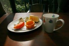 Plate of fruit and coffee mug Royalty Free Stock Image