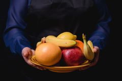 A plate of fruit in hand. Hands holding served fruit plate above hotel pool. Exotic summer diet. Tropical beach lifestyle Royalty Free Stock Photography