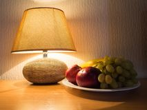 A plate of fruit next to the table lamp. royalty free stock images