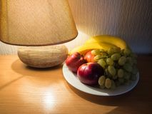 A plate of fruit next to the table lamp. stock photo