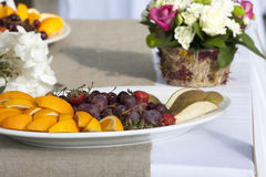 Plate with fruit on a table near  bouquet of flowers Royalty Free Stock Photo