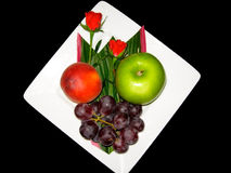 Plate of Fruits. A Plate of Delicious Fruits and Decorated with Two Red Roses royalty free stock images