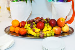 The plate of fruits and berries on white. The plate of fruits and berries on white, Serving in the restaurant. Oranges and grapes, bananas and apples, peaches Stock Images