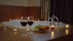 Plate with fruits and glasses of red wine for two standing near water flowing in bath. Blurred vie of plate with fruits and glasses of red wine standing in the stock footage