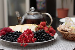A plate of fruits and red currants on the foreground Royalty Free Stock Photo