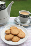 Plate full of biscuits with tea pot and a cup Royalty Free Stock Photography