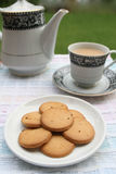 Plate full of biscuits with tea pot and a cup Stock Image