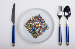 Plate full of colorful sharp thumbtacks Stock Photo