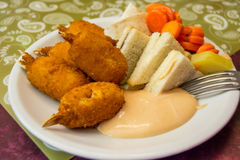 Plate full of delicious food - crab fingers, little sandwiches, carrots and mayonnaise Stock Photo