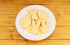 Plate full of frosted Easter cookies on a wooden table Royalty Free Stock Image