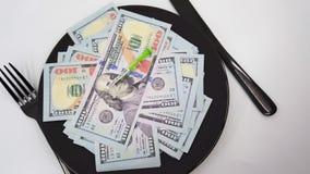 Plate full hundreds of dollar bills with fork, knife and positive COVID-19 test. Concept cost of coronavirus pandemic. Coronavirus