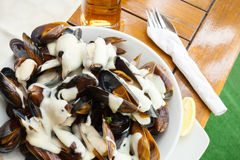 Plate full of mussels with garlic sauce on table Royalty Free Stock Image