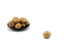 A plate full of walnuts and one walnut Royalty Free Stock Images