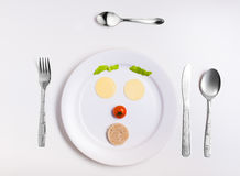 Plate with funny emoticons made from food with cutlery on white Royalty Free Stock Photography