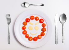 Plate with funny emoticons made from food with cutlery on white Stock Image