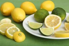 Plate fyllde med skivor av citroner och limefrukter Royaltyfri Bild