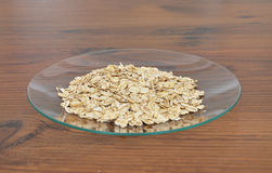 Plate of glass with oat flakes Stock Photo