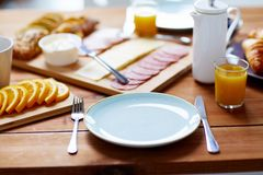 Plate and glass of orange juice on table with food Royalty Free Stock Photos