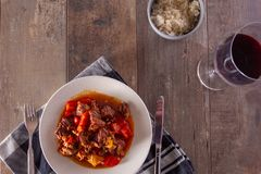 A plate with goulash or beef stew on the table. Photographed in a flat top down view royalty free stock photography