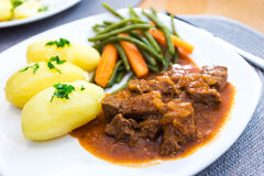 Plate of goulash. With potatoes, french beans and carrots Stock Photography
