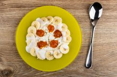 Plate with grainy cottage cheese, slices of banana, jam and yogurt, spoon on table. Top view royalty free stock images