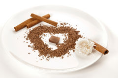 A plate with grated chocolate and sticks of cinnamon Royalty Free Stock Images