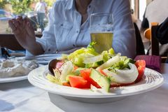A plate of a Greek salad on a table, indoors. stock photo
