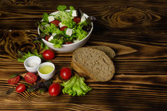 A plate with Greek salad, two cups with salt and olive oil, decorated with cherry tomatoes, lettuce leaves and bread on a wooden b. A plate with Greek salad, two Royalty Free Stock Image