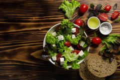 A plate with Greek salad, two cups with salt and olive oil, decorated with cherry tomatoes, lettuce leaves and slices of bread on. A wooden background. Top view Stock Photography