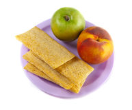 A plate with green apple, peach and three crisps Stock Photography