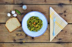 Plate of green beans. Portion of green beans, bread slices and garlic on the table Stock Images