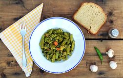 Plate of green beans. Portion of green beans, bread slices and garlic on the table Royalty Free Stock Photos