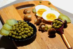 A plate of green peas with pickled cucumbers and mushrooms. Snack assorted: canned green peas, pickled mushrooms and pickled cucumbers on a black plate with a Royalty Free Stock Photos