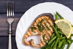 Plate of grill salmon fish with salad and fork top view closeup Stock Images