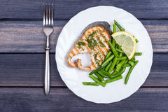Plate of grill salmon fish with salad and fork top view Royalty Free Stock Images
