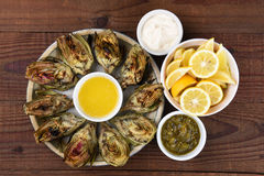 Plate of Grilled Artichokes. High angle view of a plate full of grilled artichokes on a rustic restaurant table Stock Photo