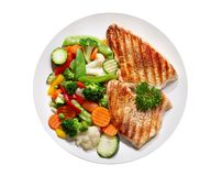 Plate of grilled chicken with vegetables on wite background, top royalty free stock photo