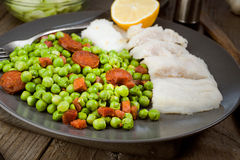 Plate of grilled fish and cooked with ham and chorizo peas in ol Royalty Free Stock Photography