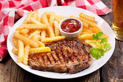 Plate of grilled meat with french fries Stock Images