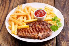 Plate of grilled meat with french fries Stock Photography