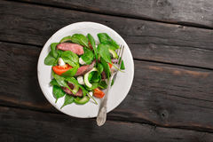 Plate with a grilled meat salad with a fork Stock Image